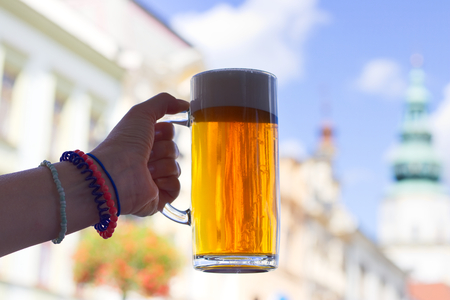 real ale: Woman holding a glass of beer in an outdoor pub in the city. A mug of draught beer.  Stock Photo