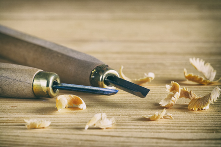Carpentry tool concept. Small chisels on a wooden board with shavings. Work with wood.  Stock Photo