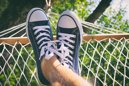 A man relaxing in a hammock in the garden. Male legs in sneakers. Chilling out in the summertime. Point of view