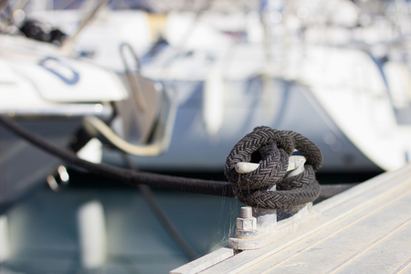 mooring bollard with rope on pier by the sea. tied yachts in the harbor