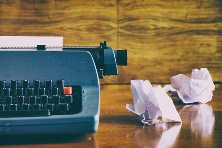 Old retro blue typewriter on a wooden desk with crumpled papers, write concept. Unsuccessfully journalist.