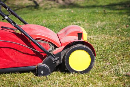 verticutter in the garden, gardener verticutting the lawn at spring, electric lawn raker