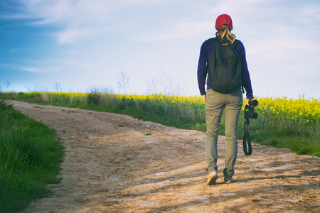 Traveler woman with binoculars is walking on footpath in the fields. Ornithologist in a countryside. Birding in nature. Stock Photo