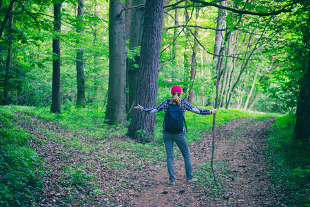 Young hiking woman does not know which way to go in green forest. A tourist girl lost herself on a hiking trip. Adventure concept.