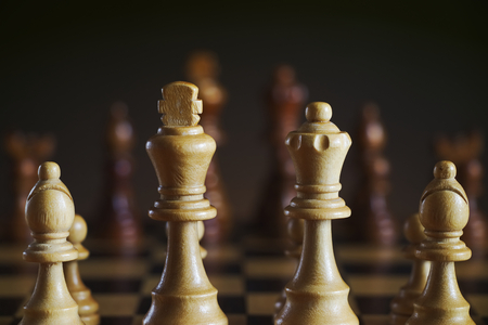 Detail of wooden white chess figures, dark background. Chess king, queen and bishop. Board game.  Stock fotó