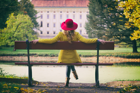 Fashion woman with red hat sitting on a bench in park and enjoying view on a castle, autumn season. Stock Photo