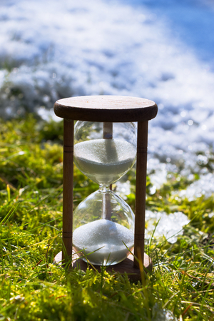 Hourglass as a symbol of climate change. Global warming. Spring is coming. Ending winter. Hour-glass in the grass and melting snow.