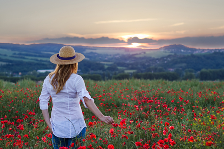 Woman standing in poppy field and enjoying a sunset. Beautiful woman wearing white shirt, jeans and straw hat. Relaxing in nature during sunset.