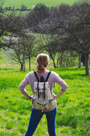 Woman traveler standing in blossoming orchard at springtime. Hiking girl with backpack at countryside.
