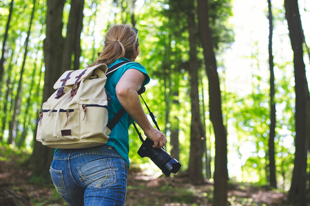 Woman photographer with camera in forest. Travelling girl with backpack climbing on hill.
