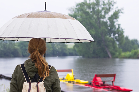 Woman with umbrella and backpack standing in rain on the riverside, rainy day, female backpacker looking to raindrops on water surface