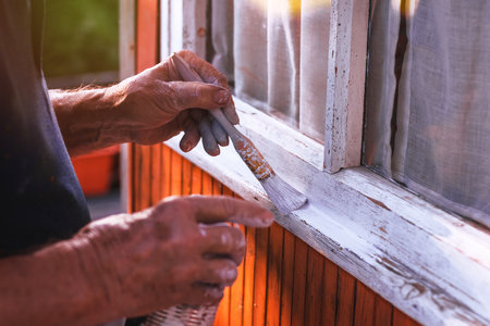 Senior man painting wooden windows using paintbrush. Repairing exterior of old house. Close-up view on old hand holding paintbrush. Foto de archivo