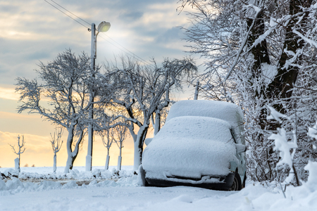 Snow-covered car parked next to road with street lights. Winter snow calamity. Reklamní fotografie