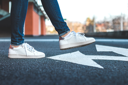 White sneakers on asphalt road with arrow traffic directional sign. Woman wearing sports shoe walking at city street