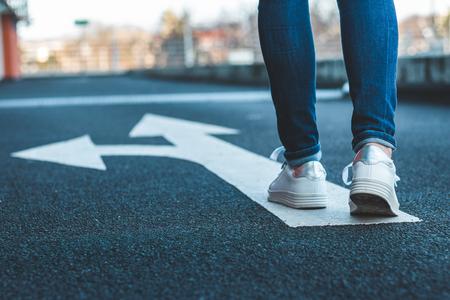 Decide qué camino tomar. Caminando sobre señal direccional en carretera asfaltada. Piernas femeninas con jeans y zapatillas blancas.