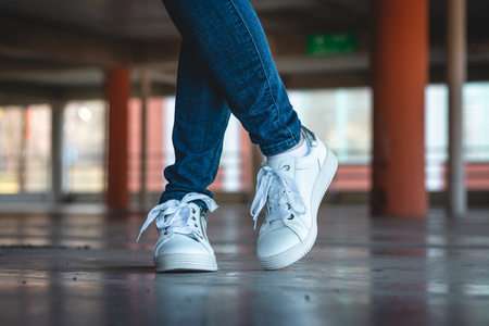 Woman with white sneakers standing in public parking garage. Fashion concept. Slim female legs wearing jeans and sport shoes in parking lot.