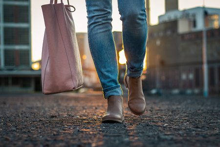 Woman in jeans and stylish leather shoe with bag walking in city during sunset. Casual clothing in city