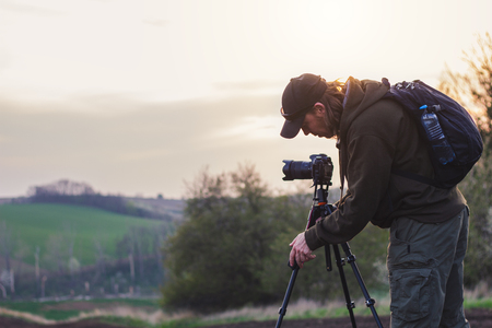 Landscape photographer setting tripod before taking picture. Man with camera outdoors during sunset Banque d'images