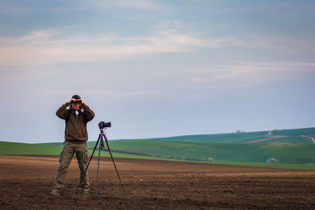 Wildlife photographer looking for animals by binoculars in nature. Rural scene know as Moravian Tuscany, Czech Republic 免版税图像