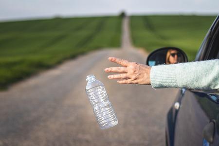 Bestuurder gooit plastic fles weg uit autoraam op weg. Milieubehoud. Plastic vervuilingsconcept