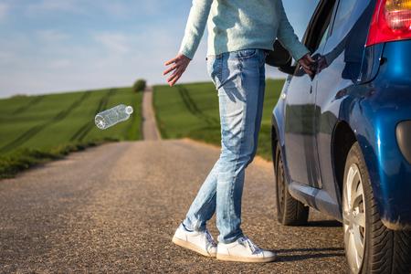 Conductor irresponsable arrojando una botella de agua en la carretera. Concepto de contaminación plástica. Conservación medioambiental
