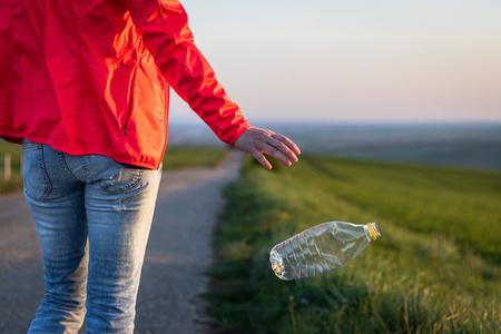 Mano che butta via la bottiglia di plastica in natura. Danni ambientali da rifiuti di plastica Archivio Fotografico
