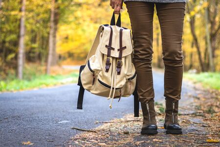 Woman with backpack wearing hiking boots is standing on road in autumn forest. Travel concept. Hitchhiker standing on roadside 免版税图像