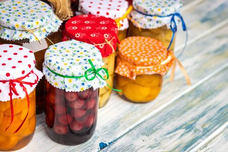 Fruity compote. Homemade preserved food in jar on white wooden table. Variety of fruit compotes