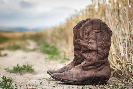Stivale da cowboy su strada sterrata accanto al campo di grano. Vecchia scarpa di cuoio consumata all'aperto. Natura morta in stile retrò di calzature nella scena rurale