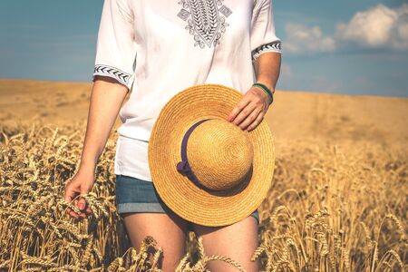 Woman wearing casual clothing and enjoying summer in field. Woman holding straw hat in her hand and staying in rural scene Banco de Imagens