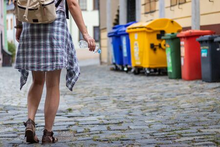 Keep clean city. Tourist holding plastic bottle and going to recycling bin. Woman and garbage bin on street
