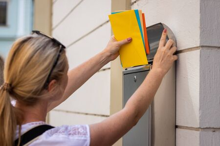 Postal worker is inserting letters into mailbox. Woman is holding colorful envelopes. Mail carrier delivering correspondence