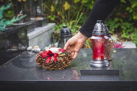 Witwer legt Kranz auf Grabstein auf dem Friedhof. Traurige Erinnerungen für Tote an Allerseelen. Mann am Friedhof Standard-Bild