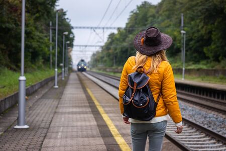 Woman with backpack and hat is looking at arriving train at railroad station platform. Traveler at beginnings of her journey Reklamní fotografie