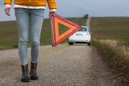 It is important to have car insurance. Driver holding warning triangle on road because car is broken. Safety first.