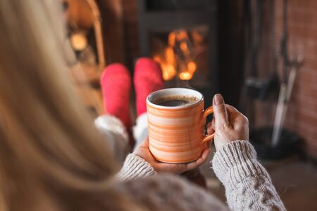 Woman is drinking hot coffee and sitting in front of fireplace. Woman relaxing in living room. Home sweet home