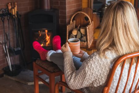 Woman is drinking hot coffee in front of fireplace and warming her feet with wool socks. Woman relaxing in living room. Home sweet home