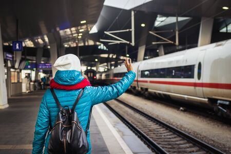 Young woman waving to leaving train at railway station. Public transportation in city. Backpacker at railroad station in winter. Travel concept
