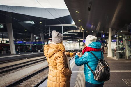 Two women waiting for train at railway station and checking time. Delay train. Transportation and travel concept