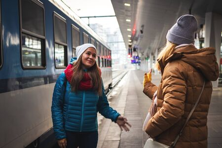 I miss you already! Two women friends say goodbye at the train station before travel. Travel concept with two persons. Railway transportation
