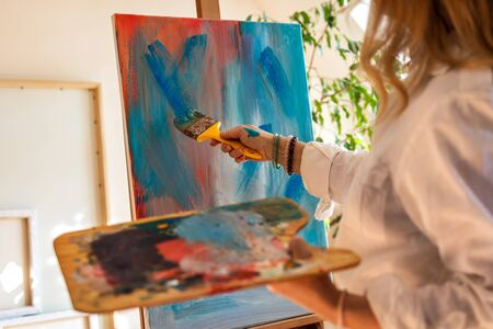 Female artist drawing acrylic painting on easel at her atelier. Woman holding palette and creates acrylic abstract paintings in studio Фото со стока