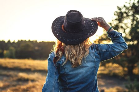 Blond hair woman with hat and denim jacket enjoying sunset outdoors. Fashion concept with woman wearing trendy casual clothing in nature at summer