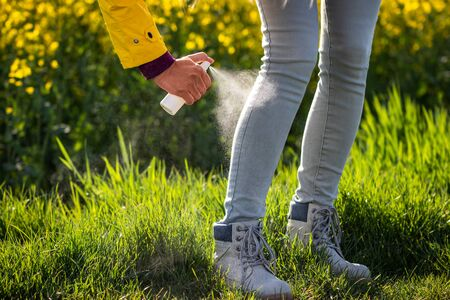 Tourist spraying insect repellent on legs and hiking boots. Protection against tick in nature Stock Photo