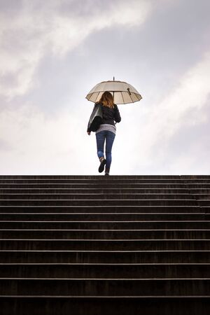 Stairway to heaven. Woman with umbrella walking at staircase in rain. Silhouette of woman against cloudy sky in city Stockfoto