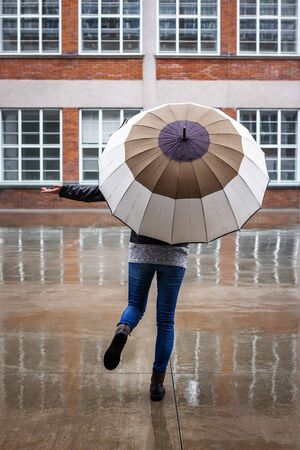 I am happy when it rains. Woman with umbrella enjoying rain in city. Rear view of carefree woman running at street