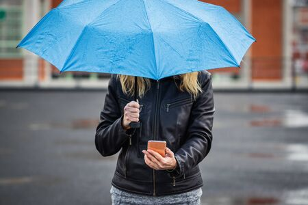 Woman with umbrella holding smartphone and standing in rain at street. Wireless internet connection on mobile phone in city