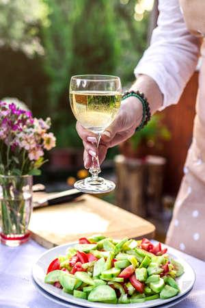 Woman enjoying white wine during preparing vegetable salad outdoors. Preparation for garden party or celebration event Reklamní fotografie