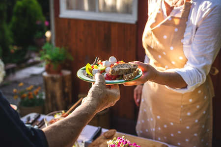 Woman serving vegetable salad with baguette on plate to another person at garden party. Catering service at celebration event outdoors Stock Photo