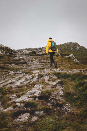 Hiking in mountain. Tourist walking up to hill. Adventure in nature. Woman with backpack wearing sports clothing Фото со стока