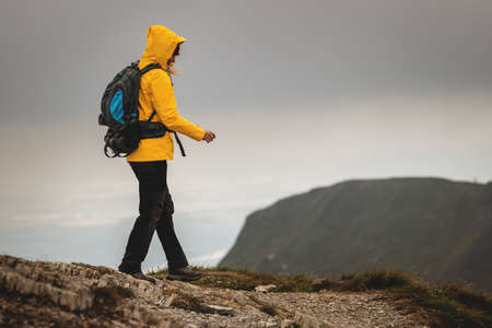 Hiking safely in mountain. Watch your step during hike and bad weather. Woman wearing yellow raincoat with backpack walking on cliff